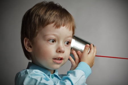 boy listening to tin can telephone